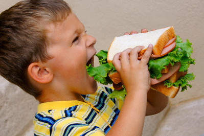 Kid eating huge sandwich t9c60o