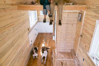Couple with dog inside tiny house kg2ibj