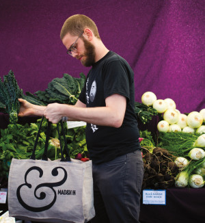 Holdfast Dining chef Will Preisch selects produce at the Hillsdale farmers market.