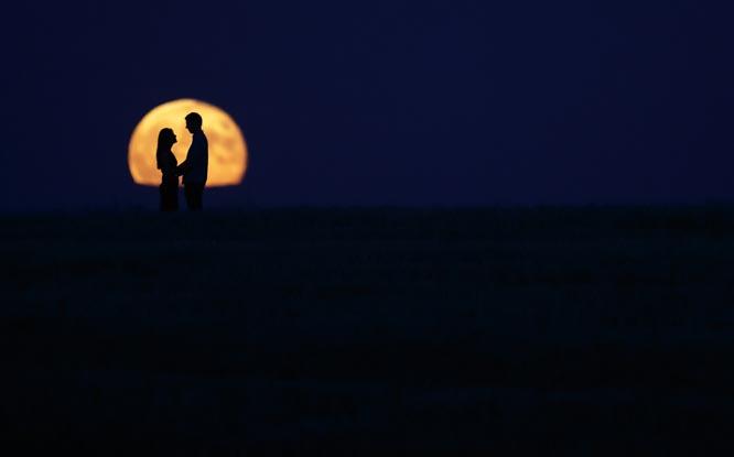 Her er et par fotografert foran supermånen i den spanske byen Burgos i går. (Foto: AFP/Scanpix)