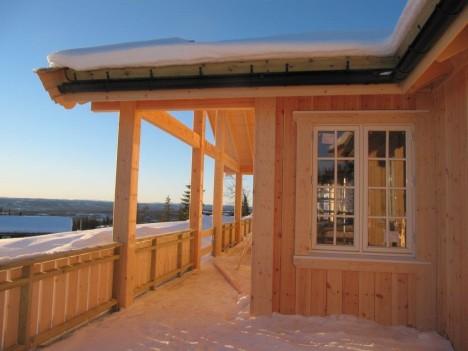 UTVENDIGE DETALJER: Delvis overbygget terrasse, stående falset panel og innramming rundt vinduene er noe vi har spesialbestilt på hytta vår.