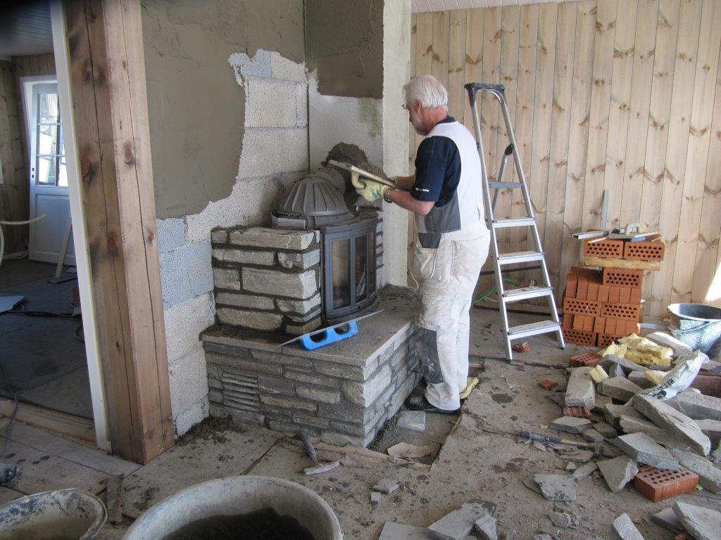 PEISEN REISER SEG: Murmester Arvid Halvorsen bygde peisen vår stein for stein. Her pusser han brannmuren før selve kappa skal lages. Innsatsen står allerede der den skal.