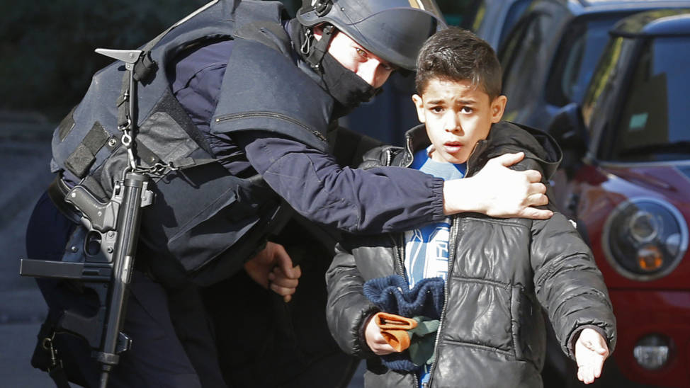 A French police officer speaks to a child as he secures an access to a school at the Castellane housing area in Marseille