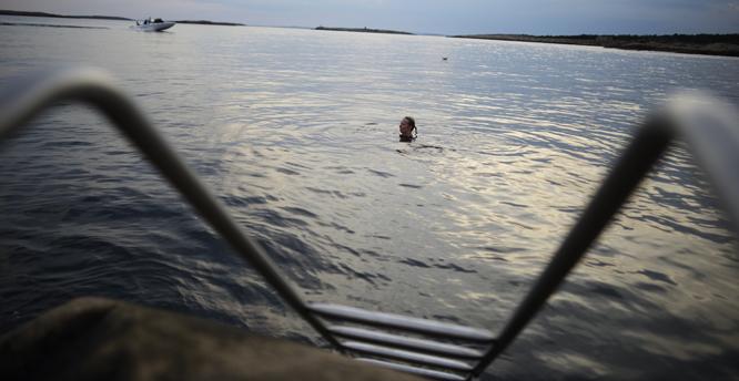 Kvinne bader mens fritidsbåt kjører i bakgrunnen. Mærrapanna, Fredrikstad kommune, Østfold. NB: Modellklarert.   Foto: © Thorfinn Bekkelund / Samfoto
