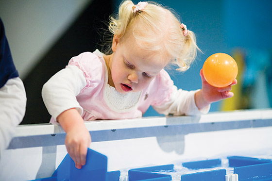 A young child plays at the water table at Great Lakes Children Museum in Traverse City