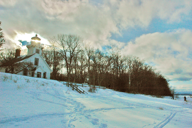 A last bit of afternoon sunlight gleams through the tower of the Mission Point Lighthouse
