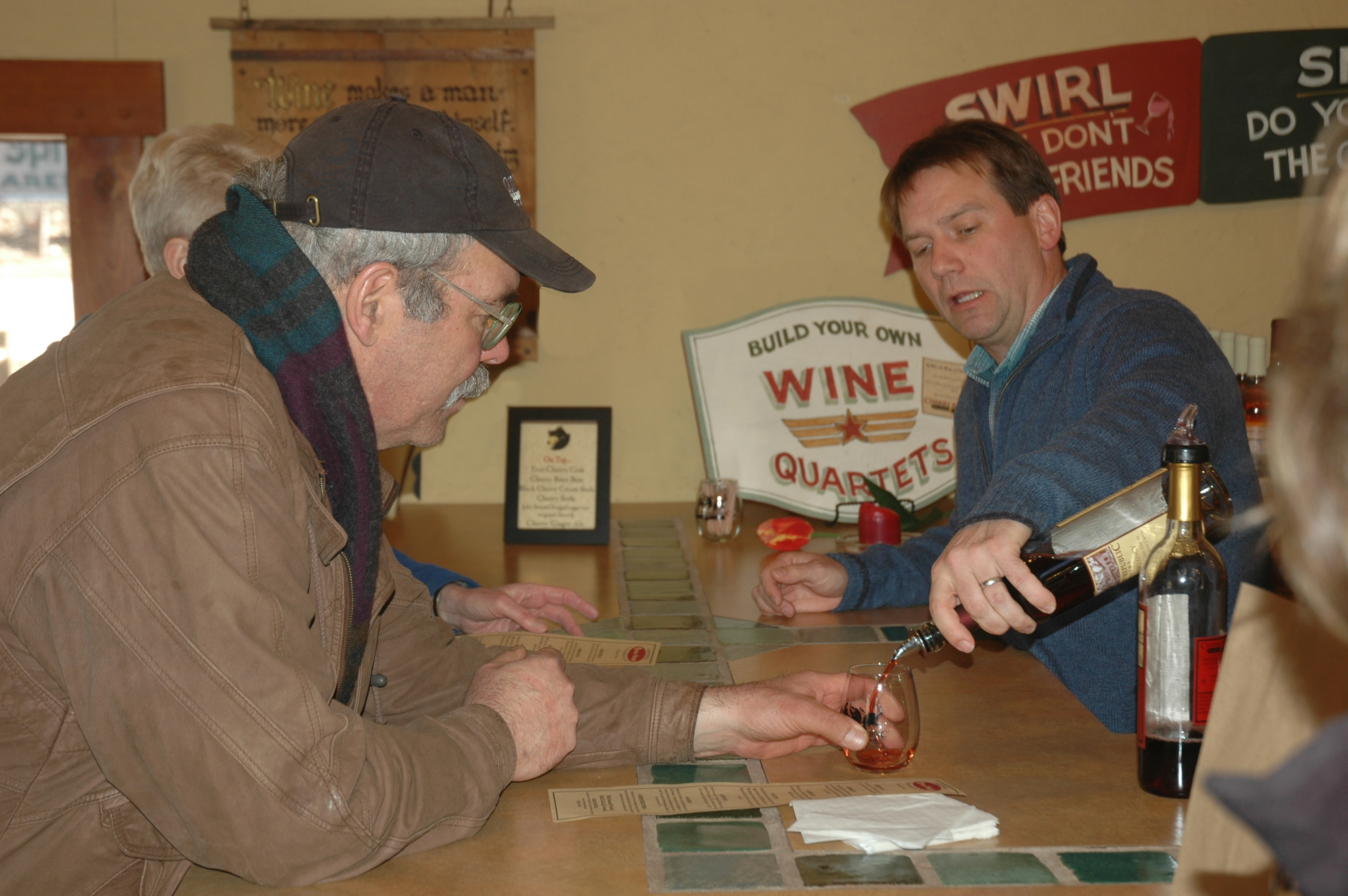 Jason Homa of Cherry Republic pours a sample of their Conservancy wine for Charlie Wunsch of Edible Grand Traverse.
