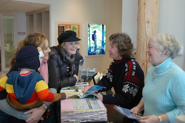 Volunteers Sherry Freels (second from right) and Sally Bell (far right) offer advice to a visiting family at the Traverse City Visitor Center.