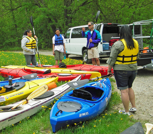 Jeff Neumann explains the basics of kayak equipment to a group of new paddlers he guided down the Grand River. Credit: Howard Meyerson