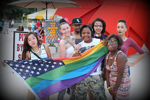 Young women posing with flag at GR Pride 2014