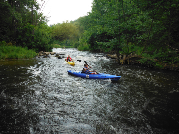 GR Paddling customers enjoy a run through the Childsdale rapids at the on the Rouge River. Credit: Jeff Neumann