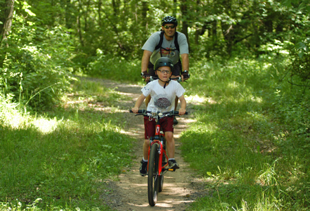 A father and son riding the mountain bike trail at Kent County's Luton Park.
