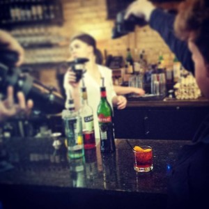Bartop with bottles and a female bartender in Grand Rapids