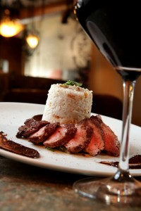 Steak dish with wine glass from Bar Divani in Grand Rapids