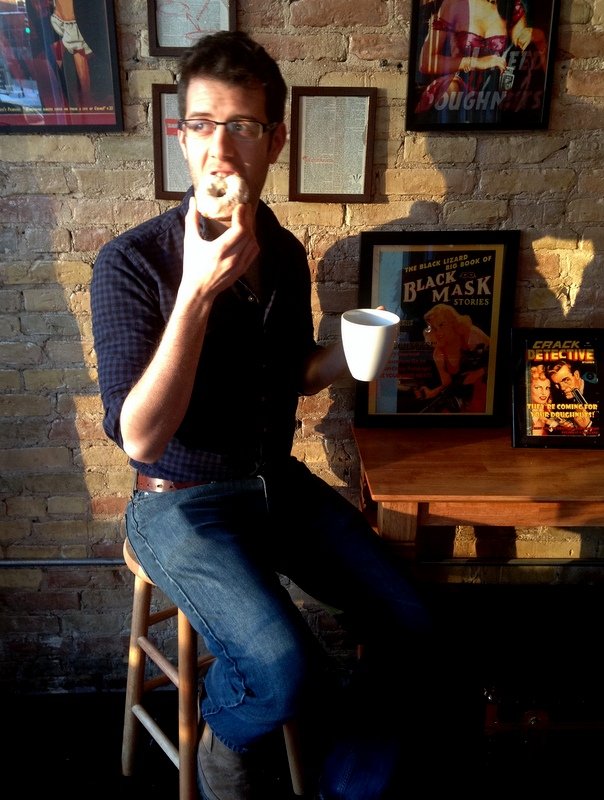 Torrence O'Haire, owner of Propaganda Doughnuts, enjoying a doughnut and coffee.