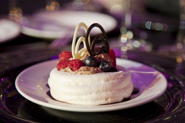 Meringue shell filled with mousse and garnished with delicate bush berries