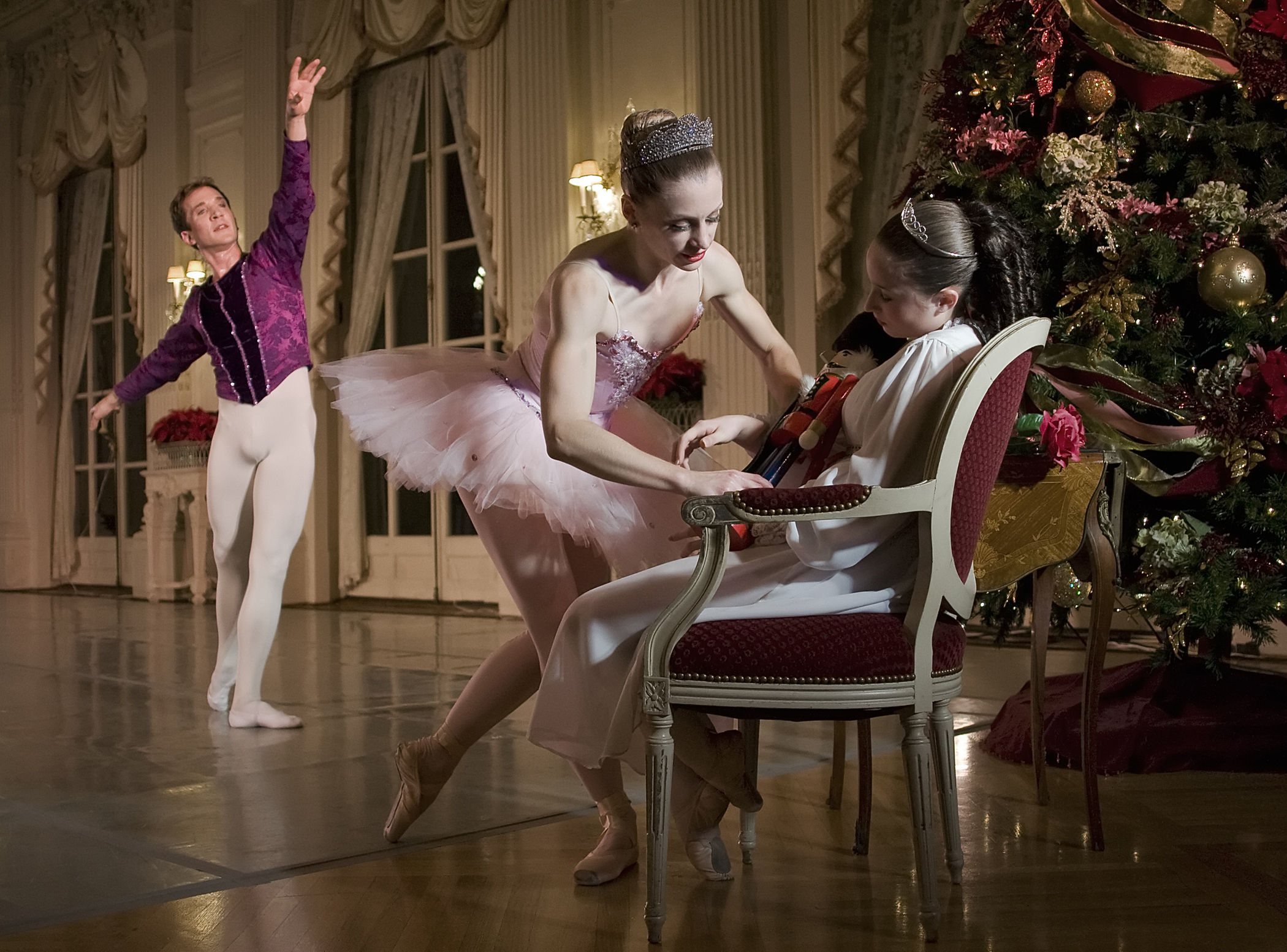 Gregg Saulnier as the Cavalier watches as Danielle Genest as the Sugarplum Fairy place the Nutcracker on the lap of the sleeping Tess (Hayden Maguire) in Island Moving Co.'s Newport Nutcracker at Rosecliff.