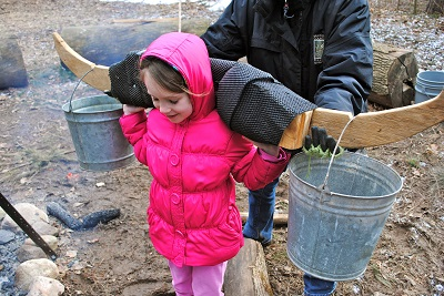My daughter at Maple Sirup Days in McCloud Nature Park in North Salem, Indiana, learning how sap from maple sugar trees was transported in colonial days.