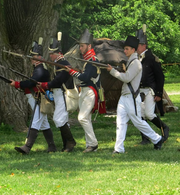 1812 re-enactors hurry across the grass of the Fort
