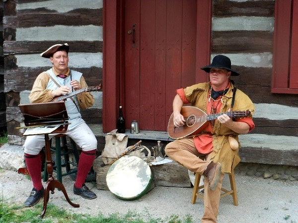 Two men in 1770s clothing play musical instruments