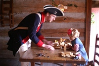 Kids and historical re-enactors work on crafts at the Christmas at the Fort