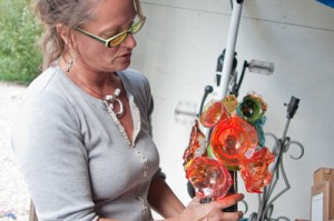 Glass artist Lisa F. Pelo holds one of her recent pieces. The creation process involved in making a piece like this flower sculpture often requires the help of an assistant or two.