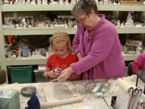 Sally patiently teaches a young artist how to make a pumpkin at Sally Ann's Ceramics.