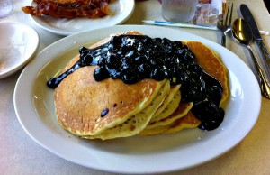 Blueberry Pancakes with lots of blueberries and syrup and a side of bacon.