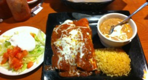 Enchiladas filled with ground beef and served with refried beans and rice.