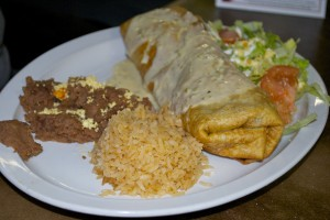 J's Chimichanga, covered with jalapeno cheese sauce and served with refried pinto beans and rice.