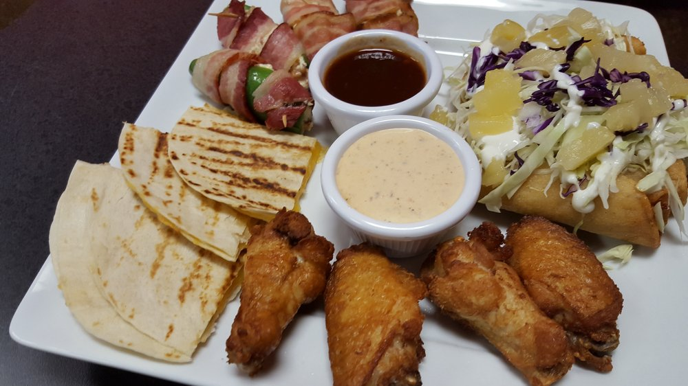Sample platter with quesadillas, chicken wings, and taquitos