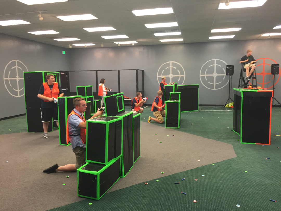 A group of young adults having a nerf gun war at Blaster Tag