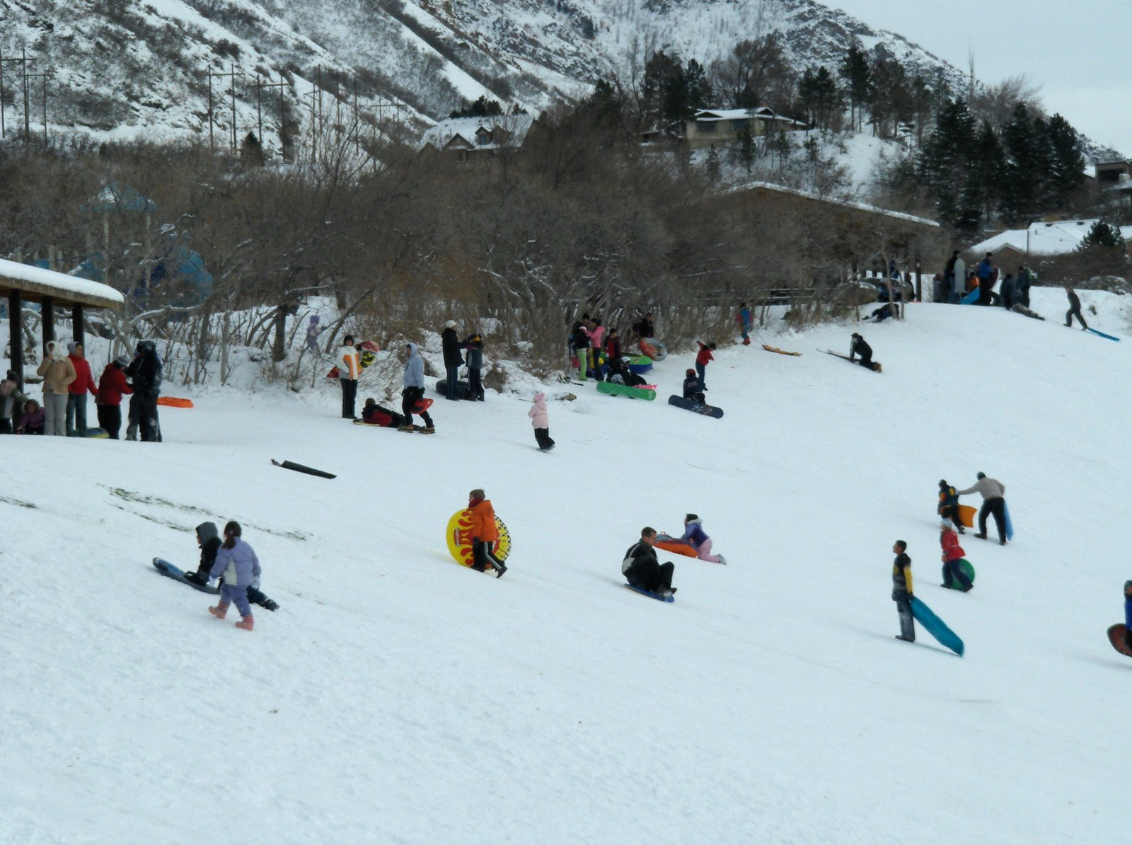 People sledding down the hill at Rock Canyon Park in Provo