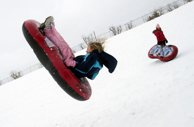 Little girl getting some serious air on a sled