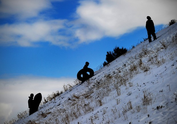 Kids walking up a hill with sleds