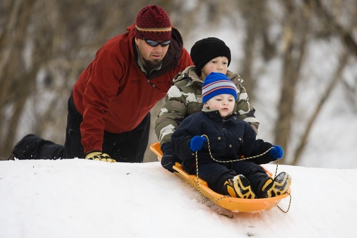 Father pushes his children's sled down the hill