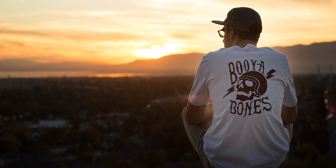Skater boy wearing a booya shirt looking over the valley