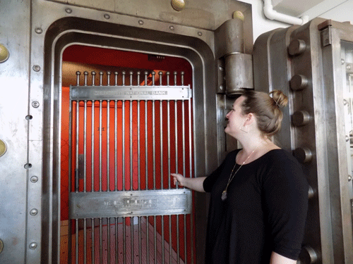 Owner Emily Peterson closes the gate on the vault (which now leads to the restrooms) where Merchants Pub & Plate found their name.
