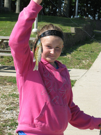A participant in the 2012 Kids' Fishing Derby, part of Free Fishing Weekend, shows off her catch. Photo Credit: Dave Kittaka