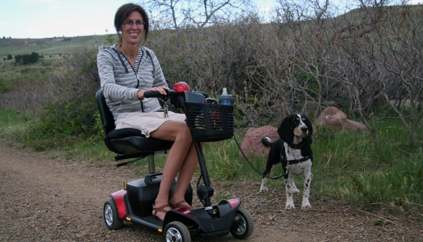 A lady uses a scooter on a Boulder trail with her service dog