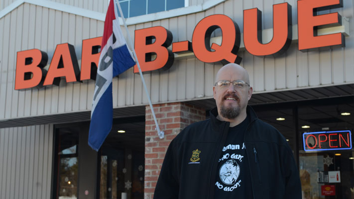 Bob Shoudt poses outside his sponsor, Phamous Phil's BBQ