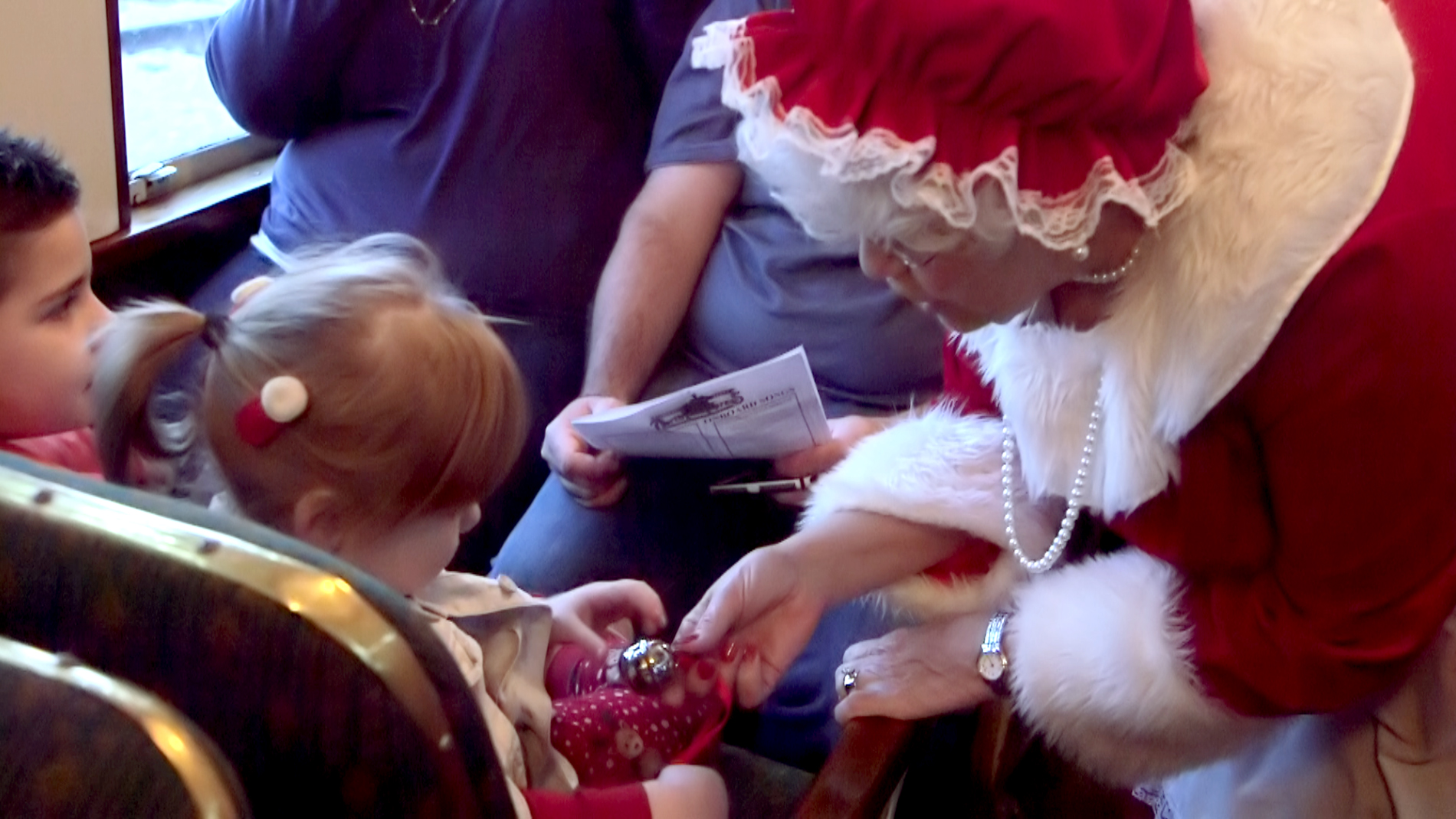 Mrs Claus Sharing A Silver Bell With the Children
