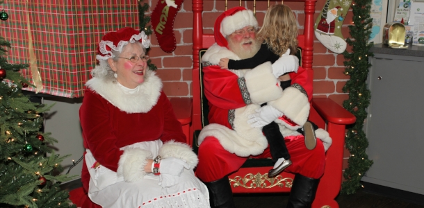 Santa hugging a child at St. Nick on the Bricks