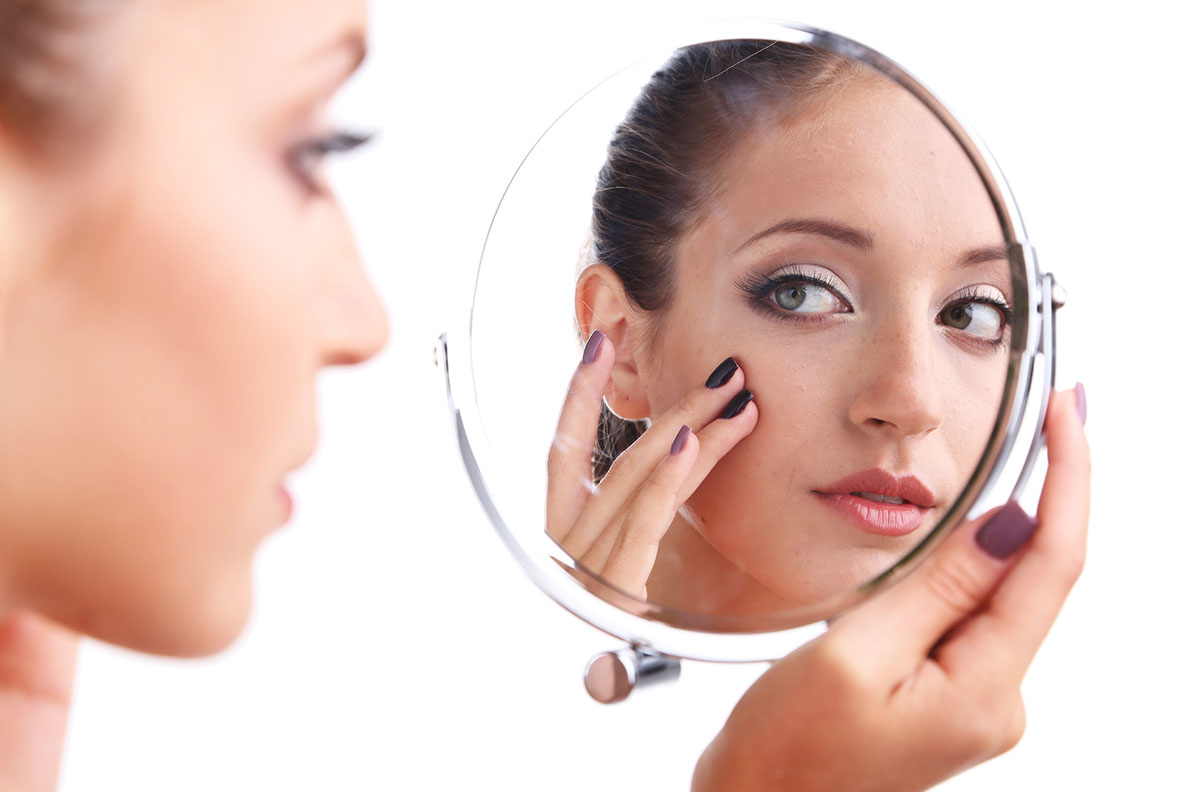 Woman looking at herself in mirror.