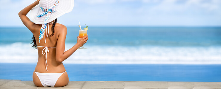 Woman enjoying a drink on the beach with smooth hair free skin.