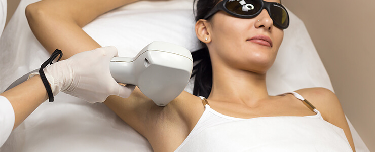 Woman getting laser hair removal on her armpits