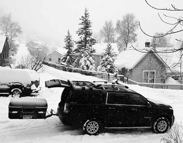Snow falling on GMC Yukon XL with StowAway MAX Cargo Carrier