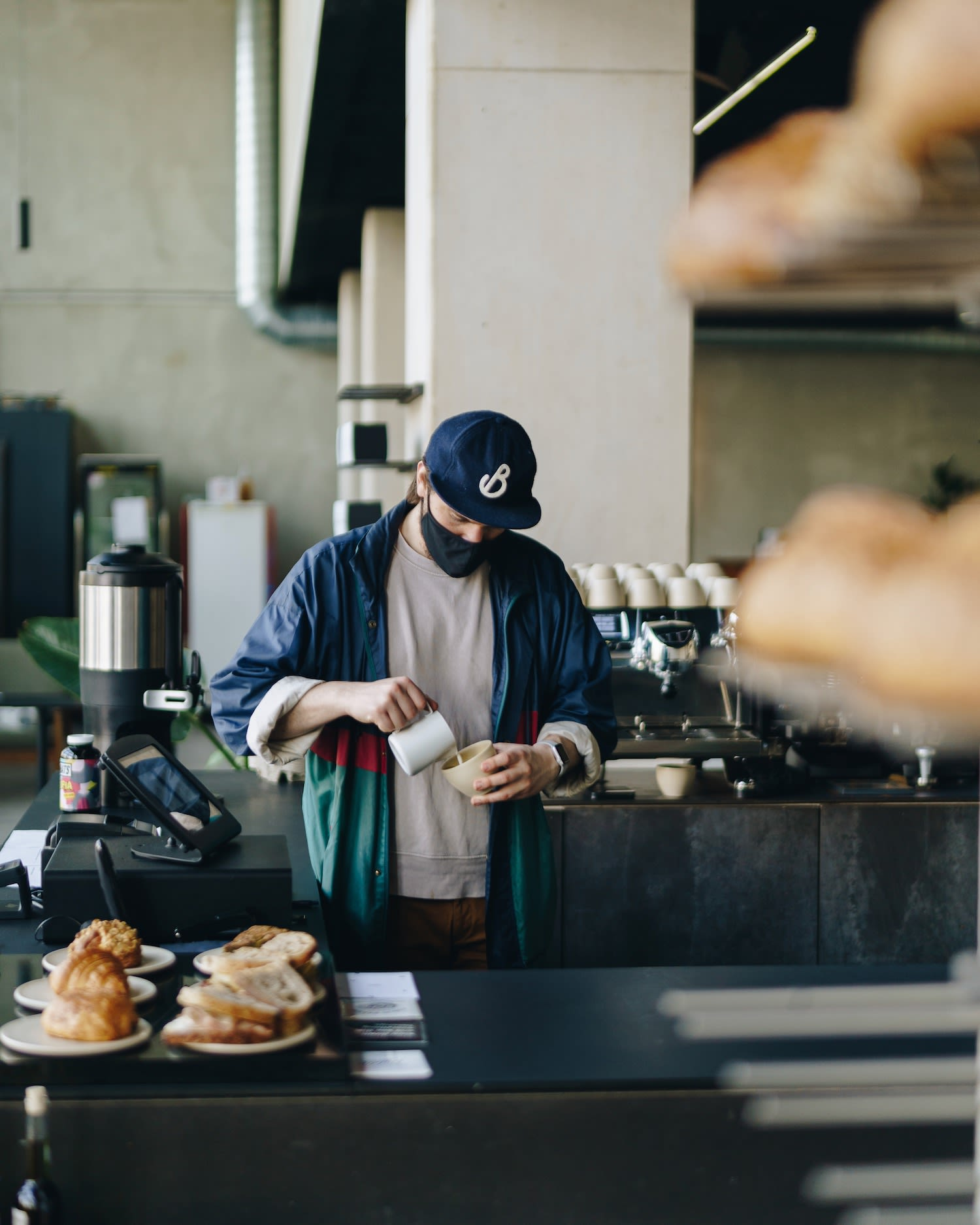 Barista from top Amsterdam coffee house Public Space pours coffee in industrial style open space with fresh pastries on display | latte art | Table Sage's Spring Favorites in Amsterdam Noord