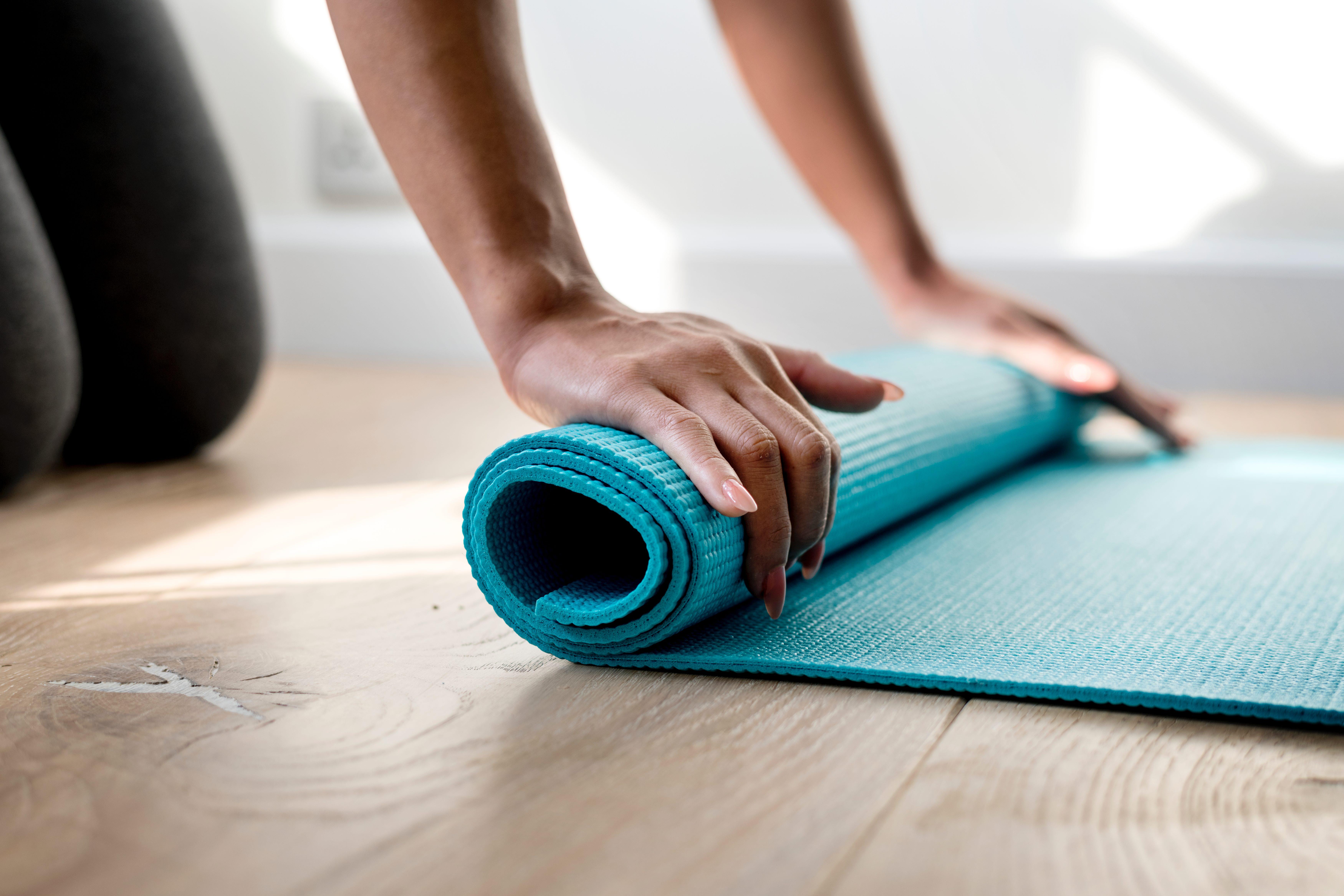 Frau rollt eine Yogamatta am Boden aus