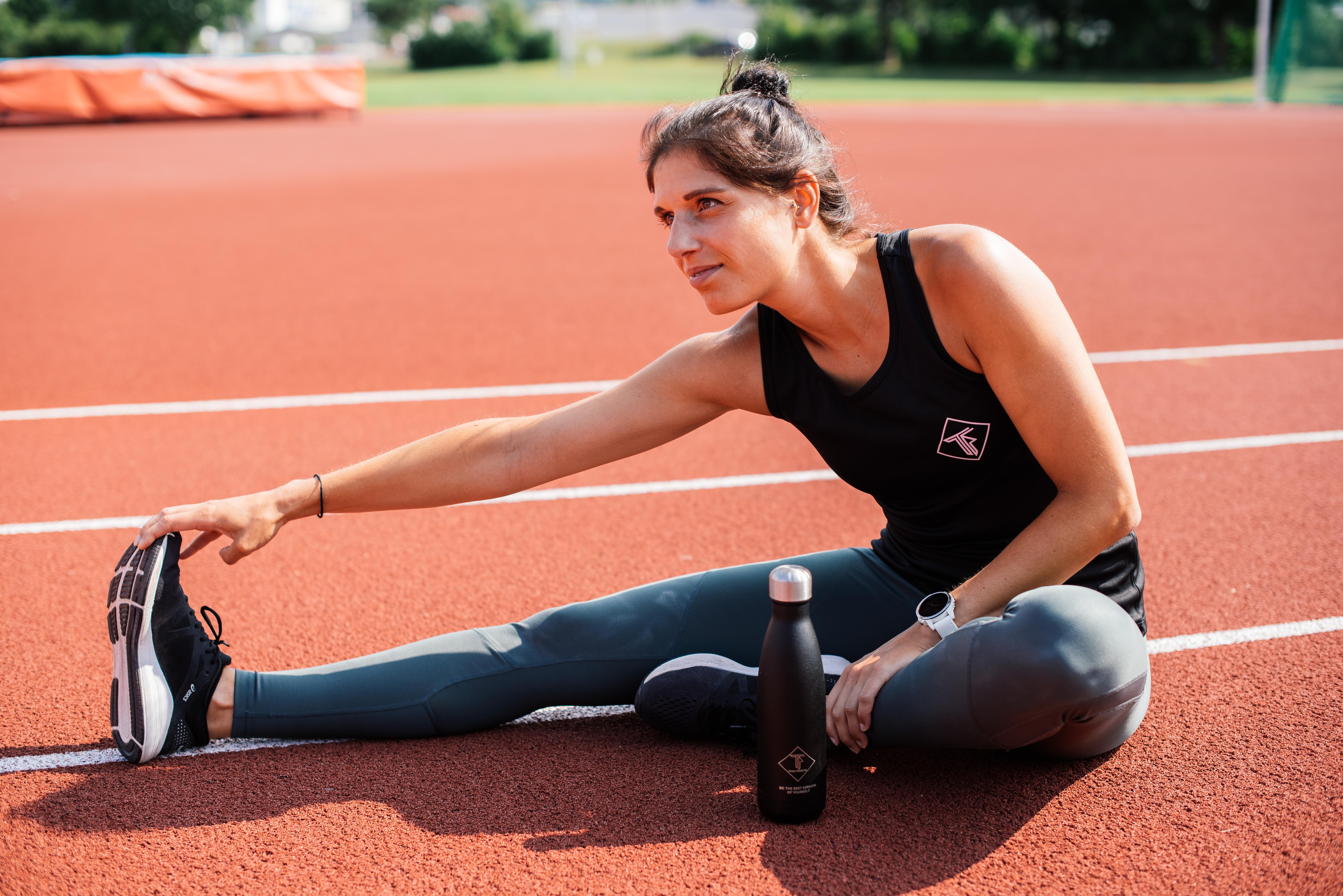 Tania dehnt die Beine nach einem Lauftraining